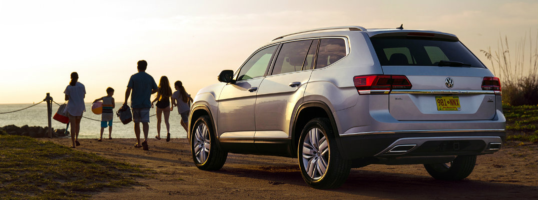 2019 Volkswagen Atlas exterior rear shot at sunrise parked at a beach cliff as a family heads towards the water