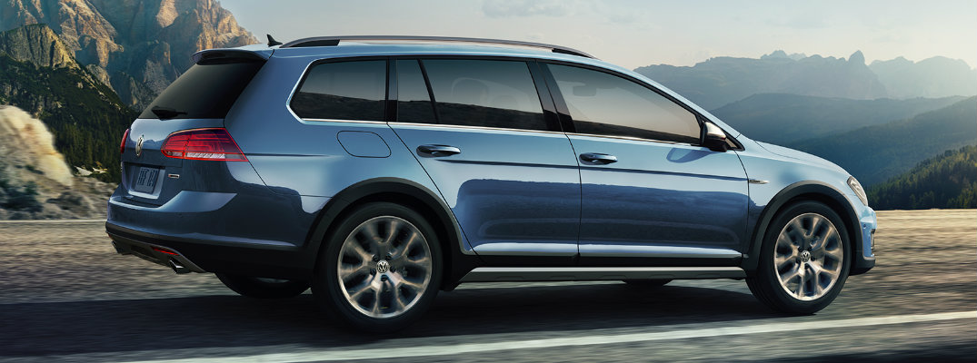 2019 Volkswagen Golf Alltrack exterior side shot with blue green tourmaline paint color driving down an open mountain road