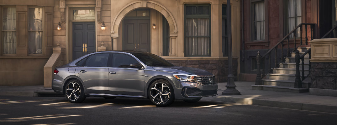 2020 Volkswagen Passat exterior side shot with gray metallic paint color parked outside a series of olf fashioned brick buildings and a victorian streetlight lamp