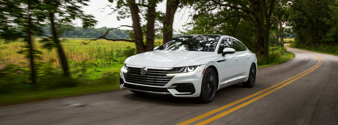 2019 Volkswagen Arteon R-Line exterior shot with white paint color driving through a wooded road of trees