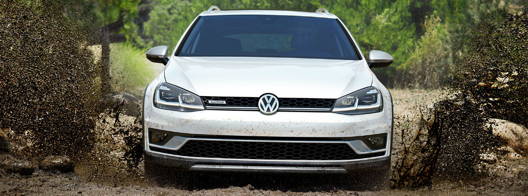 2019 Volkswagen Golf Alltrack exterior front shot with pure white paint color driving through a muddy off-road path