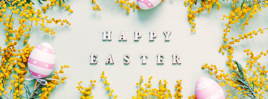 Happy Easter spelled out with letters set into green wood and surrounded by flowers and painted Easter eggs