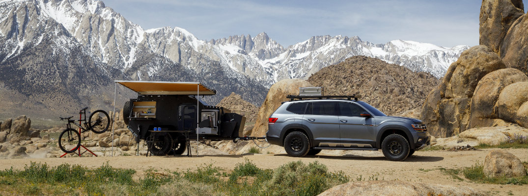 Volkswagen Atlas Basecamp Concept exterior side shot parked in the mountains with a trailer set up as a camp