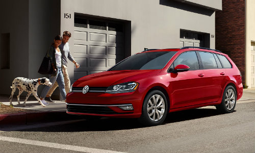 2019 Volkswagen Golf SportWagen exterior shot with tornado red paint color with a couple walking their dalmatian dog by