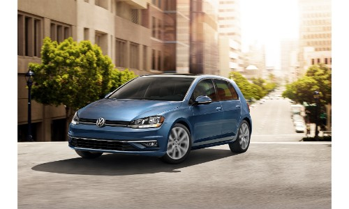 2019 Volkswagen Golf exterior shot with blue paint color driving through a suburban city neighborhood under the sun blog