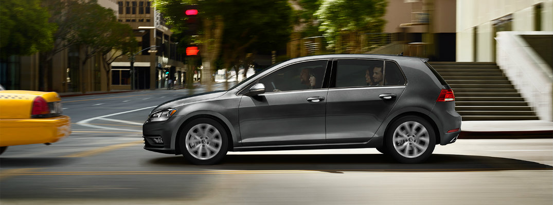 2019 Volkswagen Golf exterior side shot with gray paint color driving through a city behind a taxi with all seats filled