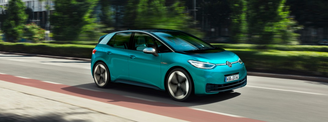 Volkswagen ID.3 compact electric vehicle exterior side shot with teal green paint color driving in a city near a line of grass and trees