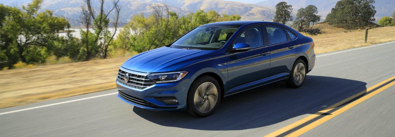 Blue 2019 Volkswagen Jetta driving down highway