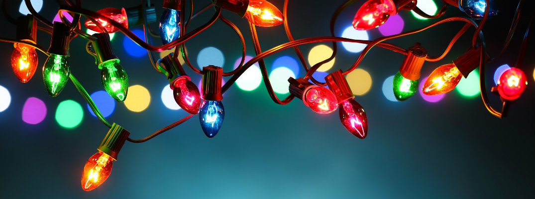 Hanging multi-colored Christmas lights with a teal blue background