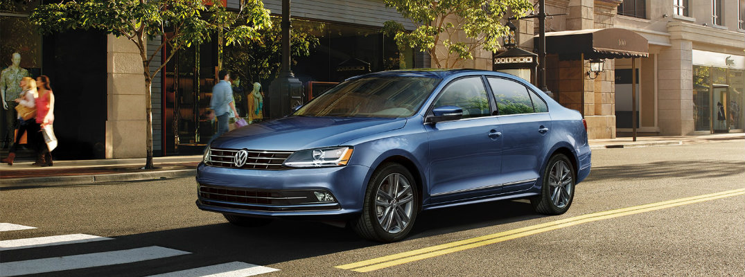 2018 Volkswagen Jetta blue parked in sunny urban city next to a crosswalk and cafe