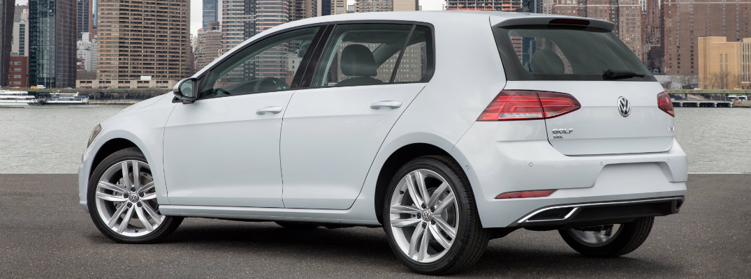 2018 Volkswagen Golf exterior side rear shot with white paint job parked on a beach with a skyscraper cityscape background