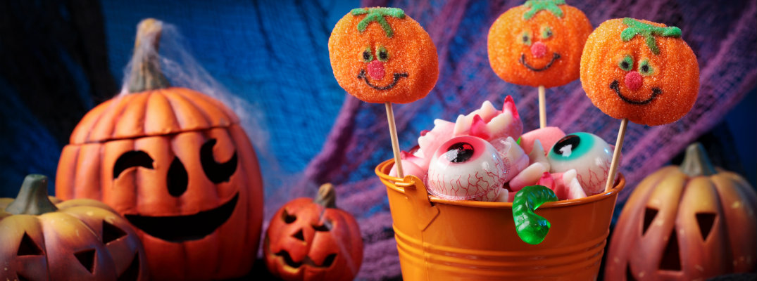 a bucket full of halloween styled treats and candy with a winking plastic pumpkin in the background