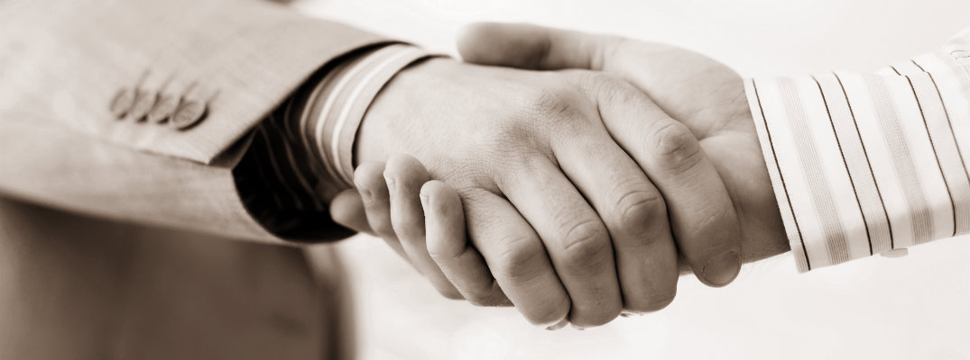 Sepia-toned image of two men doing a handshake