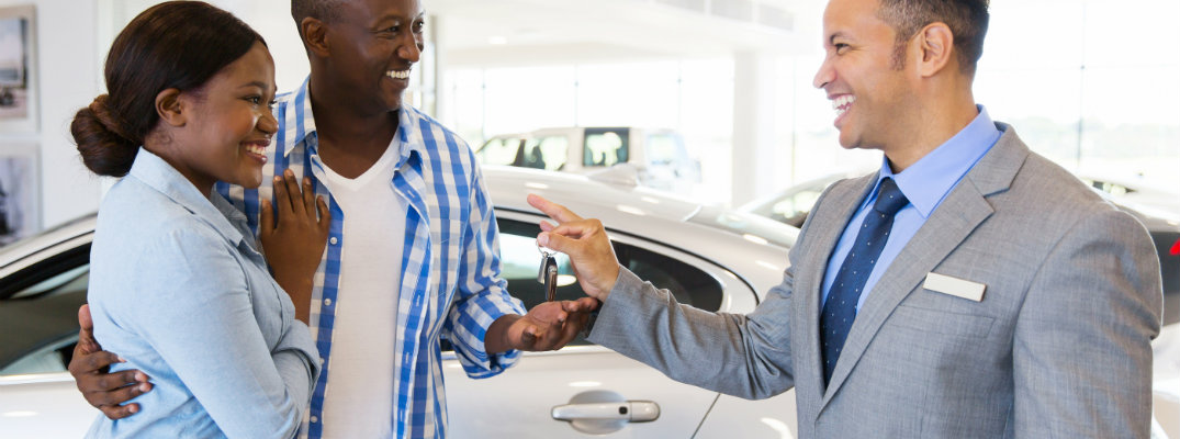 Salesman handing the keys of a new car to a couple