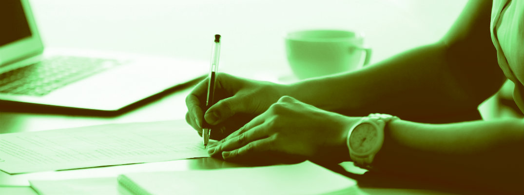 Green-tinted image of a woman signing a document
