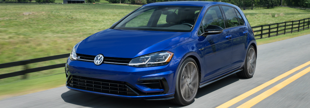 Blue 2018 VW Golf R Driving by a Grassy Field