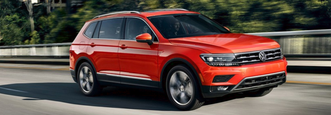 Orange 2018 VW Tiguan Driving by a Forest