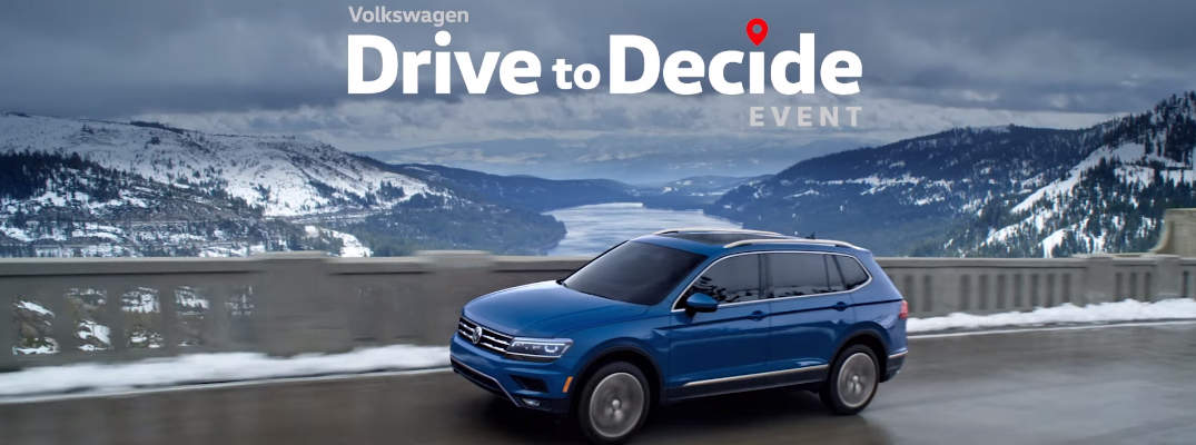 Volkswagen Drive to Decide Event title and a Blue 2019 VW Atlas driving across a snowy bridge