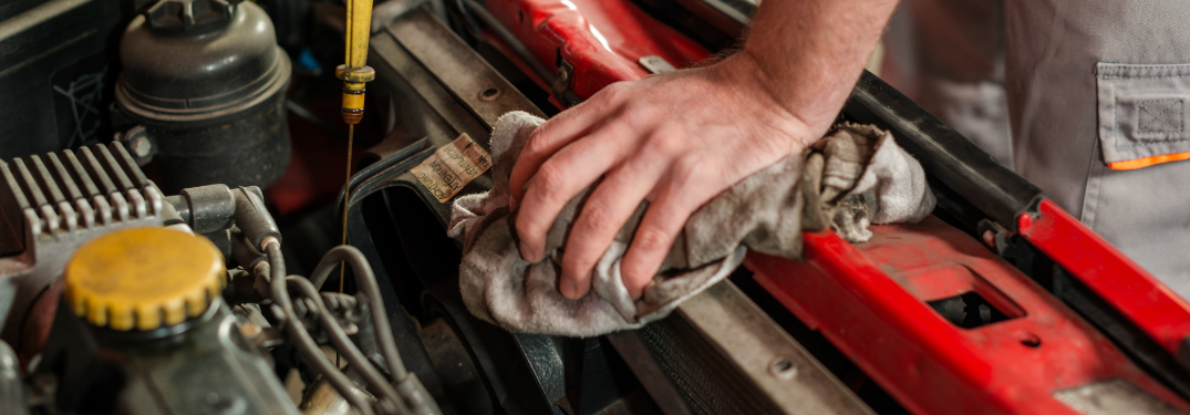 Automotive technician performing an oil change on a car