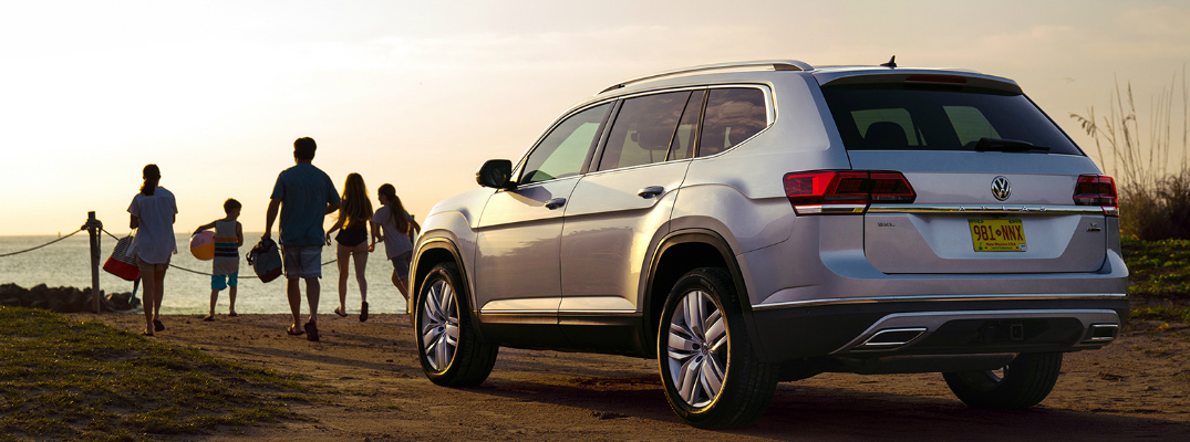 A family walking on the beach near a silver 2019 Volkswagen Atlas