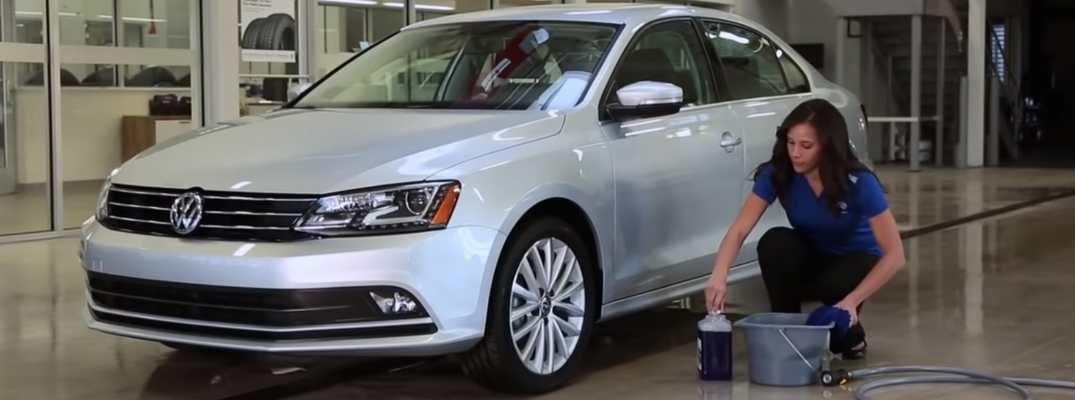A woman washing a silver Volkswagen Jetta