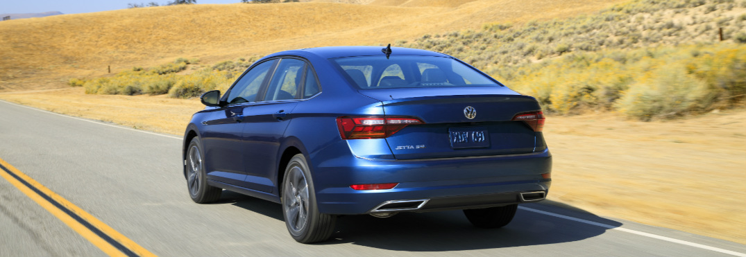 Rear view of blue 2019 Volkswagen Jetta driving on a highway