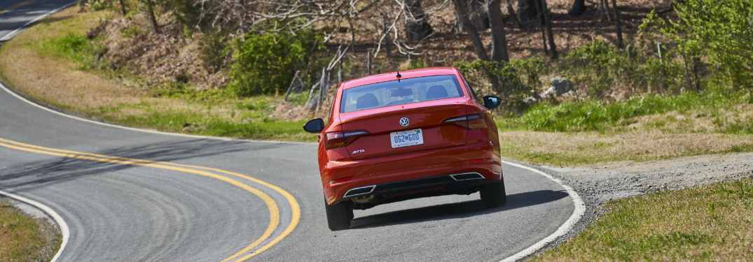 Red 2019 Volkswagen Jetta driving on a curvy road