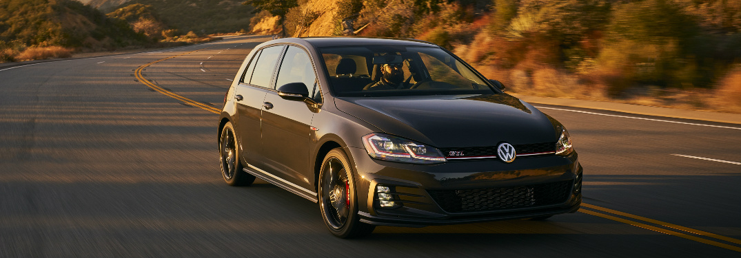 Dark grey 2019 Volkswagen Golf GTI Rabbit Edition driving on a curvy mountain road