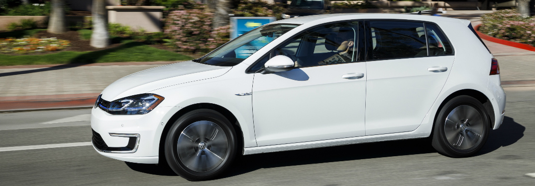 White 2019 Volkswagen e-Golf driving by palm trees