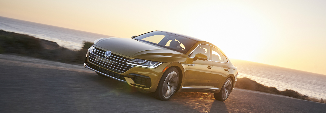 Yellow 2019 Volkswagen Arteon driving on a coastal road