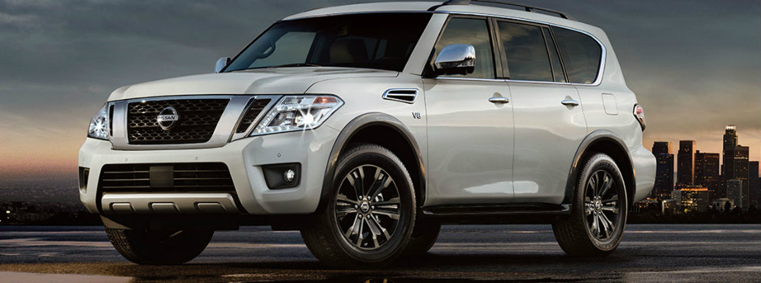 White 2018 Nissan Armada model parked in front of city skyline at nighttime