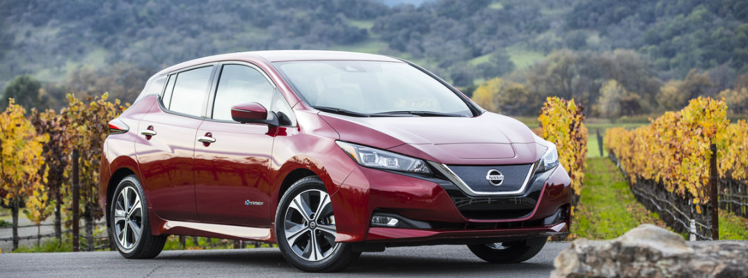 Red Nissan Leaf model parked on driveway with vineyard field in background