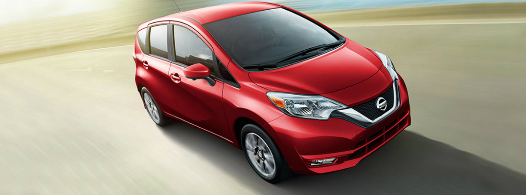 Long shot of red 2018 Nissan Versa Note driving down road in daytime