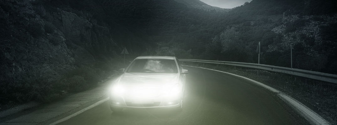 A photo illustration of a lone car driving at night with it headlights turned on