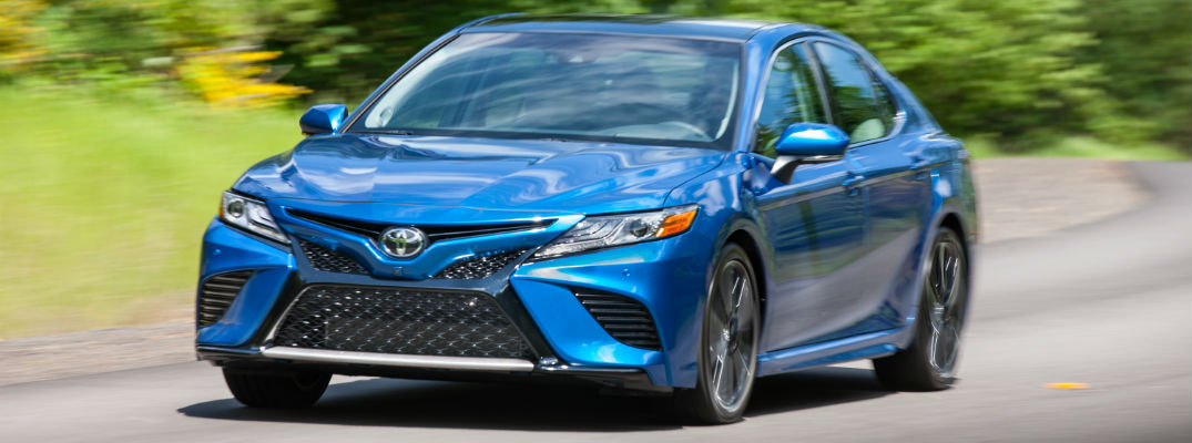 A front view of a blue 2018 Toyota Camry coming down the road