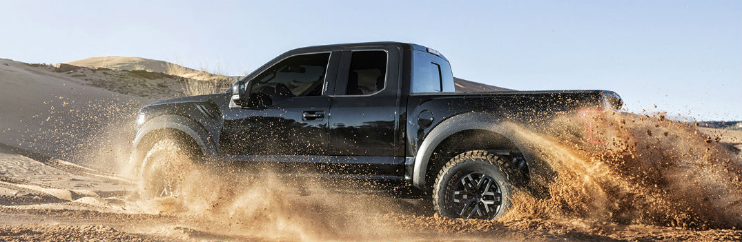 2017 ford f-150 raptor black exterior driving through sand