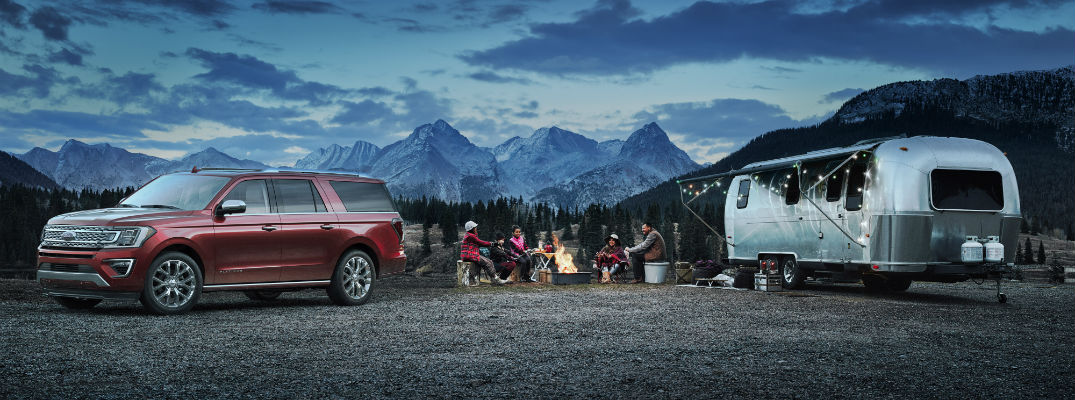 A photo of the 2018 Ford Expedition with a travel trailer out in the wilderness in front of the mountains