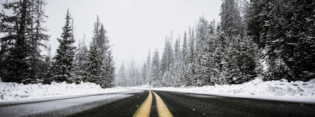 A stock photo of a desolate road during a winter snow storm