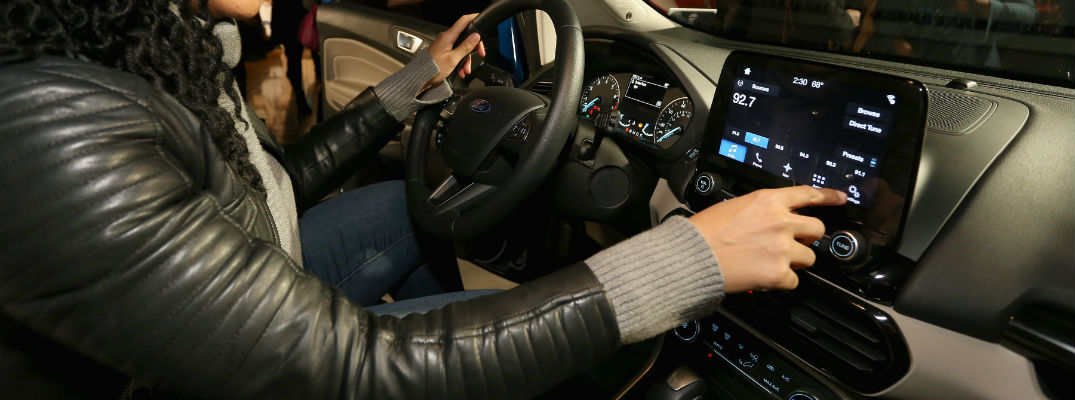 A photo of a person using the large touchscreen interface inside of the 2018 Ford EcoSport now available at Heritage Ford.