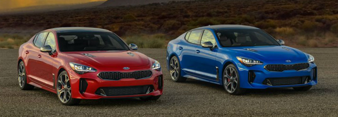 Front exterior view of a red and a blue 2018 Kia Stinger