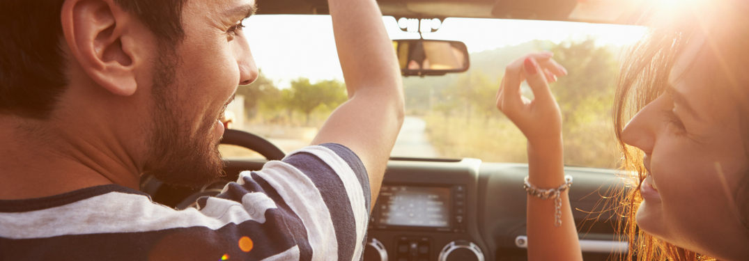 man-and-woman-with-hands-up-driving-in-convertible