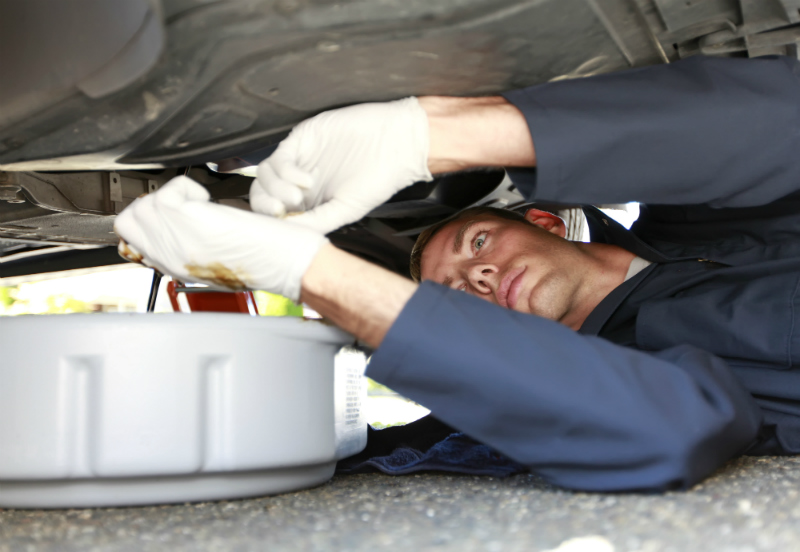 Automotive mechanic changing oil underneath a car