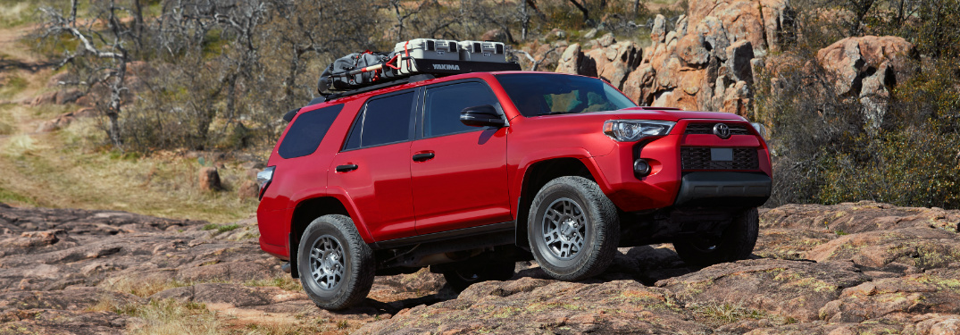 Red 2020 Toyota 4Runner Venture Edition driving over rocky terrain