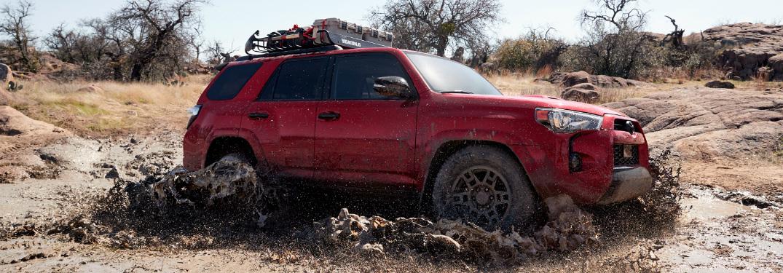 Red 2020 Toyota 4Runner Venture Edition driving through muddy water