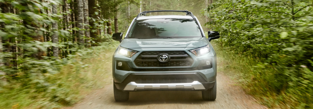 Light blue 2020 Toyota RAV4 driving on a forest road