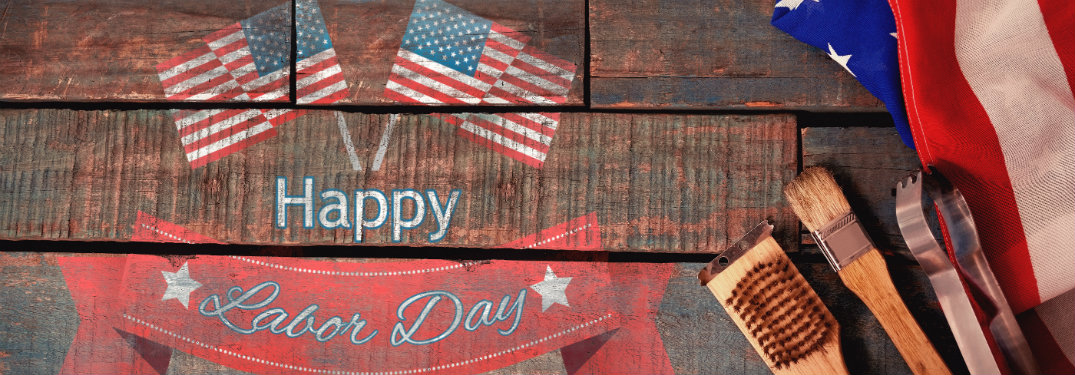 Happy Labor Day American flags and banner painted on wood planks with grilling tools