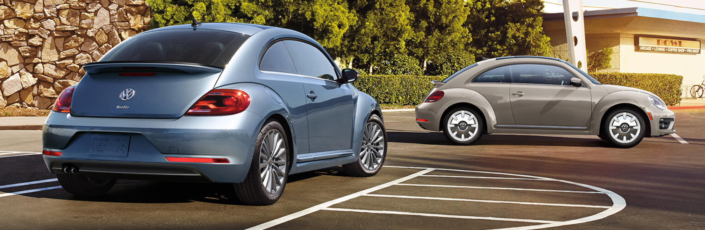 two volkswagen beetles in a parking lot