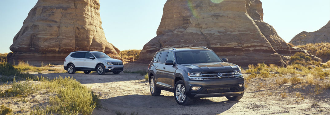 2018 volkswagen tiguan and 2018 volkswagen atlas shown in butte park against rocky hill background
