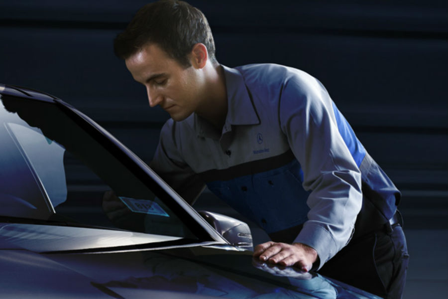 man hunched over car working on internals