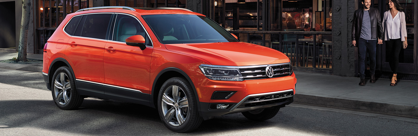 Orange 2018 Volkswagen Tiguan parked in front of a store